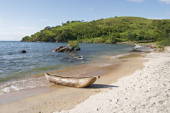 Dugout canoe, Lake Malawi. A traditional dugout canoe or bwato lies pulled up on the pebbly beach at Makuzi Bay, Malawi. A tree covered hillside forms the far stock photo