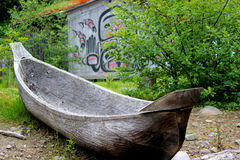 Dugout Canoe With Native Background. Native american dugout canoe on land is displayed in front of a native building Royalty Free Stock Image