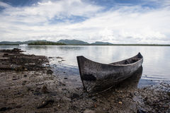 Dugout Canoe in Solomon Islands. A dugout canoe has been pulled up on a rocky beach in a remote area of the Solomon Islands. Many islanders still use canoes and royalty free stock photography