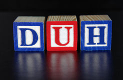 DUH. The concept of DUH in blue and red toy blocks on a black background. Horizontal Stock Photos