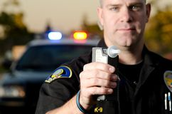 DUI Breath test. A police officer holds up a breath test machine at a DUI stop Royalty Free Stock Photography