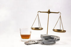 DUI Legal Concept. DUI lawyer concept of miniature car with glass of whiskey, handcuffs and legal scales of justice on white Royalty Free Stock Photo