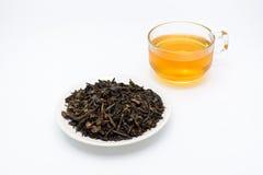 Duidelijk glas thee en droge theebladen in een kop op wit Stock Afbeeldingen