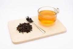 Duidelijk glas thee en droge theebladen op houten plaat Stock Fotografie
