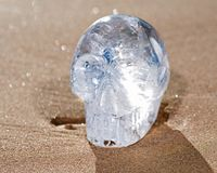 Duidelijk Kwarts Gesneden Crystal Skull op het strand bij de zonsopgang stock foto