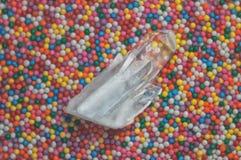Duidelijk mystiek gefacetteerd kristal van kwarts chalcedony op een multicolored close-up als achtergrond Prachtig mineraal stock foto