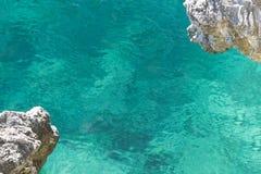Duidelijk turkoois zeewater met een mening van de bodem en het overhangen van de hoeken van de rots stock afbeelding