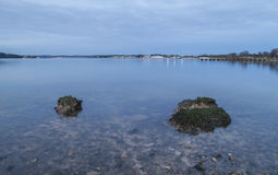 Duidelijk water in baai met rotsen en lichten bij schemer Stock Foto's