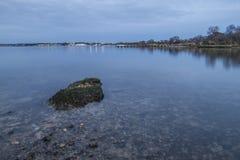 Duidelijk water bij schemer in baai met rots Royalty-vrije Stock Afbeeldingen