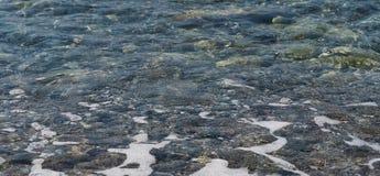 Duidelijk water en kleurrijke kiezelstenen op het overzees stock fotografie