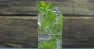 Duidelijk water in glas met groene muntbladeren en ijsblokjes stock video