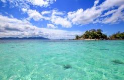 Duidelijk zeewater en blauwe hemel met wolken Stock Afbeeldingen