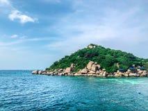 Duidelijk zeewater op het strand met een eilandachtergrond royalty-vrije stock afbeeldingen