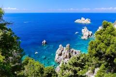 Duidelijke blauwe Griekse rotsachtige kust bij paleokastritsa Stock Afbeeldingen