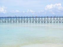 Duidelijke blauwe overzees, hemel, witte wolken en houten brug Stock Foto
