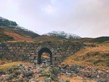 Duidelijke gebogen stroomrivier onder oude steenachtige brug De weg van bergschapen Stock Fotografie