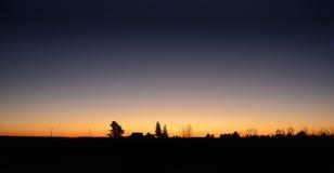 Duidelijke hemel met oranje zonsondergang gesilhouetteerd landschap Royalty-vrije Stock Fotografie