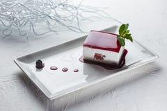 Duidelijke kaastaart die met fruitjam met een laag wordt bedekt op een vierkante plaat royalty-vrije stock fotografie