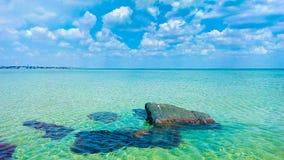 Duidelijke overzees met witte wolken en steen royalty-vrije stock foto