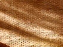 Duidelijke stevige oranjegele bakstenen muur met schaduwen van de zonachtergrond Stock Afbeeldingen