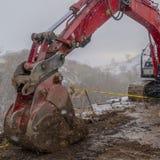 Duidelijke Vierkante Rode graafwerktuig en barricade op een modderige die bergweg in de winter wordt bekeken stock foto's