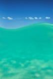 Duidelijke waterlijn Caraïbische overzees onderwater en over met blauwe hemel Stock Afbeeldingen