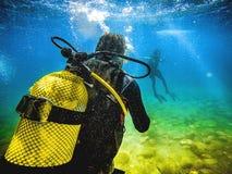 Duiker terug naar camera, die aan een andere duiker in het overzees kijken royalty-vrije stock fotografie