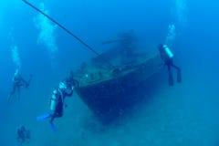 Duikers die het schipwrak in tropische overzees onderzoeken Stock Fotografie