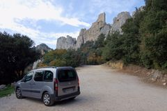 A small car repeats the silhouette of the huge Qatari castle Peyrepertuse royalty free stock photography