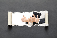 Duim op zakenlieden in gescheurd zwart document royalty-vrije stock afbeelding
