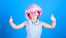 Duimen UPS voor comfortabele hoofdtelefoons Meisje in buitensporige glazen die hoofdtelefoons en roze haarpruik dragen Klein kind royalty-vrije stock foto