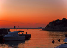 Duino, Italy - red sunset and harbor with motor boat Stock Image