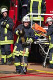 DUISBURG, GERMANY - 03 JUL 2011. An unidentified woman and man firefighter in uniform. Show a variety of instruments and tools for humans rescue and fire Royalty Free Stock Image