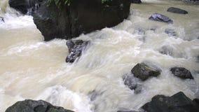 Duister Rivierwater die door rotsen met geluid vloeien stock video