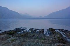 Duistere avond over meer met erachter waaier van bergen stock fotografie