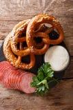 Duits voedsel: gesneden worsten en pretzels met room dicht saus Stock Afbeeldingen