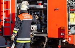 Duitse Brandweerkorpsbrandbestrijder op Brandvrachtwagen Stock Afbeelding