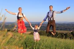 Duitse Familie in het Beierse kleding gelukkig springen stock foto's