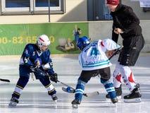Duitse jonge geitjes die ijshockey spelen Stock Foto's