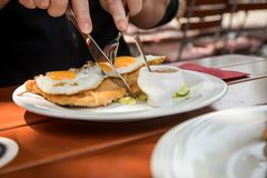 Duitse mens die de stijl van de Schnitzelhamburg van het varkensvleesvlees met gebraden binnen eieren eten, potatoe komkommersala royalty-vrije stock afbeelding