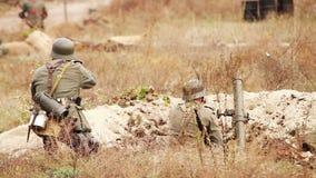 Duitse militairen die met een geweer en een mortier in geul schieten Oude de filmfilm van WO stock footage