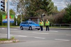 Duitse politiewagen met twee politieagenttribunes op een straat royalty-vrije stock foto