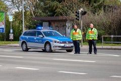 Duitse politiewagen met twee politieagenttribunes op een straat royalty-vrije stock fotografie