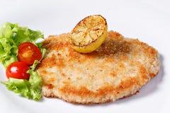 Duitse schnitzel met citroenen en kalk, tomaten en de salade van de lams` s sla stock fotografie