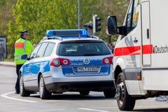 Duitse van de noodsituatieziekenwagen en politie voertuigtribunes op de straat Stock Foto