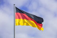 Duitse vlag die op vlaggestok golven Blauwe hemel met vele wolkenachtergrond royalty-vrije stock fotografie