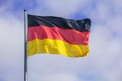 Duitse vlag die op zilveren vlaggestok golven Blauwe hemel met vele wolkenachtergrond stock foto's