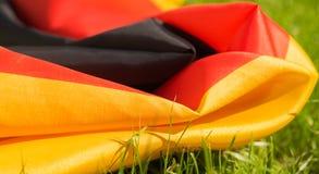 Duitse vlag op het groene gras op zonnige dag, close-up Royalty-vrije Stock Afbeelding