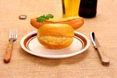 Duitse worst met horizontaal broodje, mosterd en bier, Stock Foto
