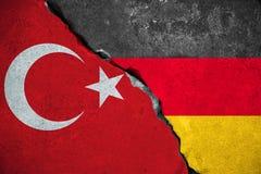Duitsland de rode Turkije vlag versus van Turkije, op gebroken schadebakstenen muur en halve de vlagachtergrond van Duitsland, de stock afbeeldingen